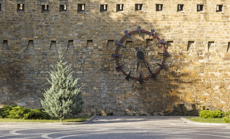 loopholes: The clock on the wall of the fortress in Baku