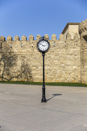 loopholes: The clock on the background of the old fortress in Baku