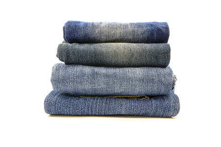 denim trousers: A stack of denim trousers on a white background