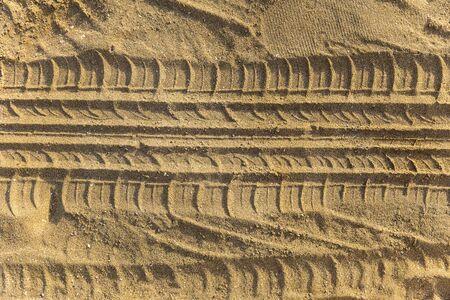rodamiento: Las huellas de la banda de rodadura de la rueda en una playa de arena