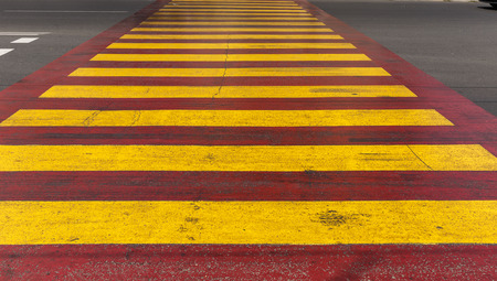 crosswalk: Red yellow crosswalk on the road