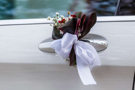 attached: Wedding decoration attached to the car door handles Stock Photo