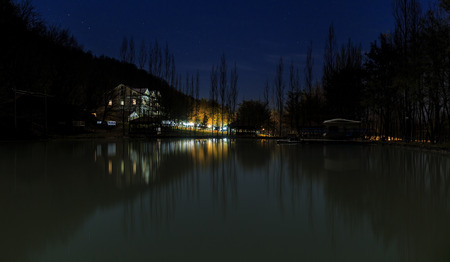 reflected: Reflected house in a lake at night in the mountains