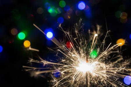 lighted: Lighted sparkler on a background garlands(soft focus)