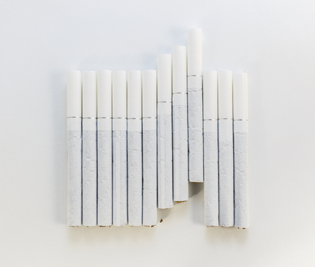 rudeness: Cigarette with a white filter laid out in a row on a white background Stock Photo