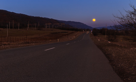 Rising moon above the road Stock Photo