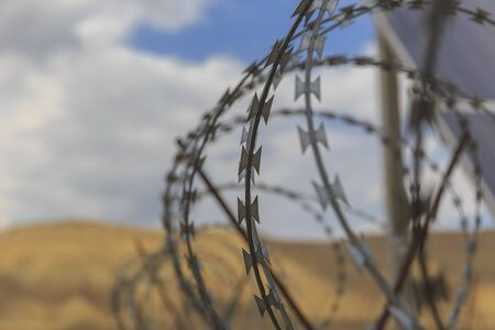 Barbed wire drawn in circles against a background of mountains