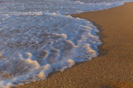 Foam from the sea water on the coast of the beach at sunset day Banco de Imagens