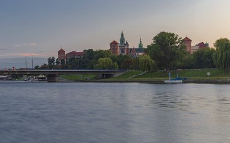 Wawel castle at sunrise reflected in the Vistula river
