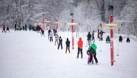 Bakuriani, Georgia - January 01, 2020: Skiers skiing climb a yoke on a mountain