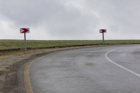 Turn Signs on a Road in the Mountains