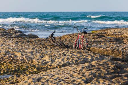 Bicycles standing between rocks on the sea coast