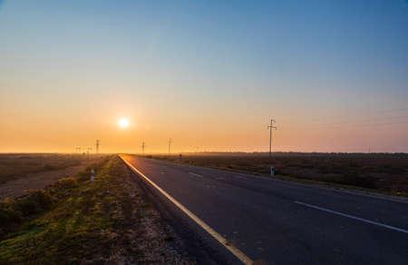 Straight asphalt road at sunrise