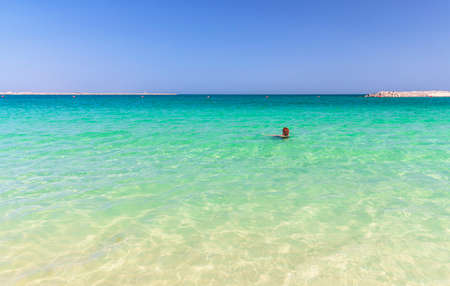 Girl swims in turquoise water on the beach