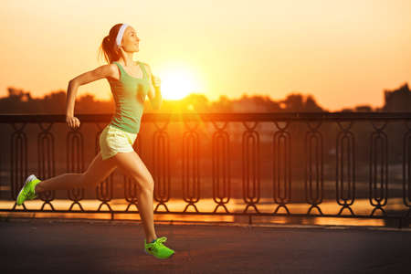 Running woman. Runner is jogging in sunny bright light on sunrise. Female fitness model training outside in the city on a quay. Sport lifestyle.