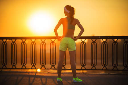 Running woman. Runner is relaxing in sunny bright light on sunrise. Female fitness model training outside and watching sunrise in the city on a quay. Sport lifestyle.