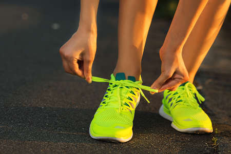 Running shoes. Barefoot running shoes closeup. Female athlete tying laces for jogging on road in minimalistic barefoot running shoes. Runner getting ready for training. Sport lifestyle. 版權商用圖片