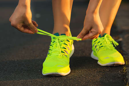 Running shoes. Barefoot running shoes closeup. Female athlete tying laces for jogging on road in minimalistic barefoot running shoes. Runner getting ready for training. Sport lifestyle. Imagens
