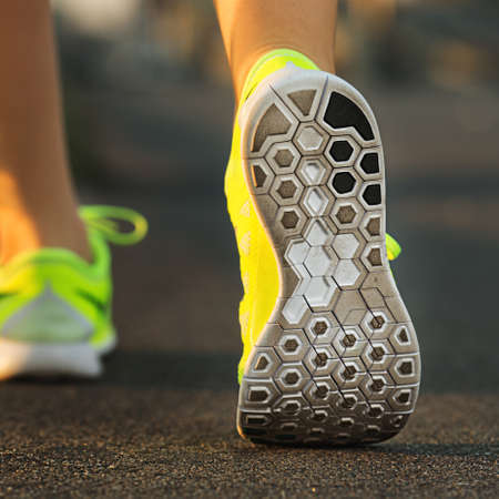 shoe model: Runner woman feet running on road closeup on shoe. Female fitness model sunrise jog workout. Sports healthy lifestyle concept.