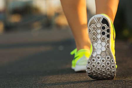 Corredor de la mujer pies se ejecutan en primer plano carretera en el zapato. Modelo femenino de fitness ejercicios de desplazamiento amanecer. Deporte concepto de estilo de vida saludable. Foto de archivo