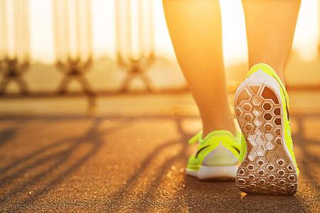 Runner Frau Füße auf der Straße Nahaufnahme auf Schuh läuft. Weibliche Fitness-Modell Sonnenaufgang Jog Workout. Sport gesunden Lifestyle-Konzept.
