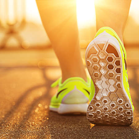 'fit body': Runner woman feet running on road closeup on shoe. Female fitness model sunrise jog workout. Sports healthy lifestyle concept.