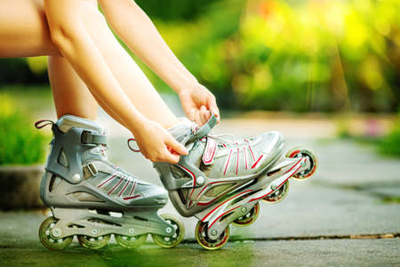 roller blade: Woman is going rollerblading. Sitting on a bench in a park and putting on inline skates. Close up. Sport lifestyle.