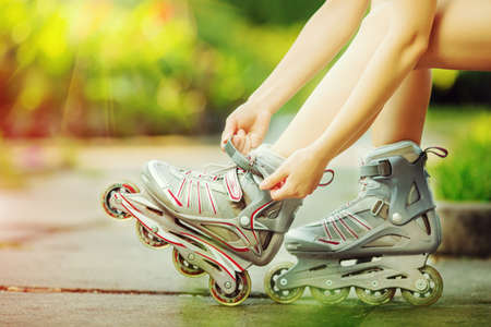 inline: Woman is going rollerblading. Sitting on a bench in a park and putting on inline skates. Close up. Sport lifestyle.
