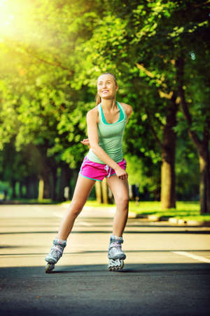 inline skater: Rollerblading woman. Young attractive female fitness model is having fun skating in a city park in the sunny morning. Sports lifestyle concept.  Stock Photo