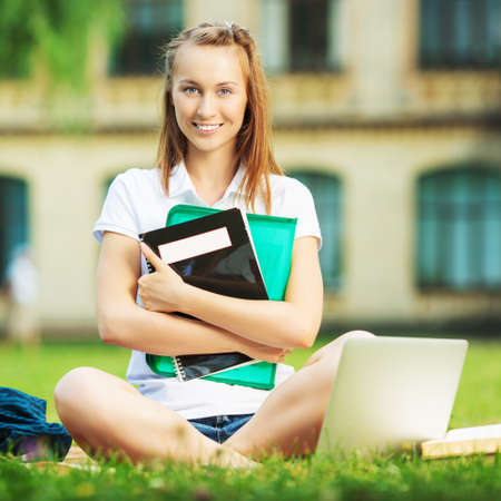 Happy pretty student woman is sitting on the lawn in the university campus with notebook in her hands and useing laptop. Study outdoors concept.  photo