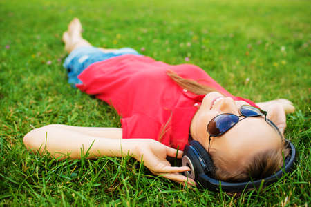 liying: Smiling young woman is listening to music in the headphones liying on the green grass and wearing sunglassed looking into the sky. Summer leisure concept. Stock Photo