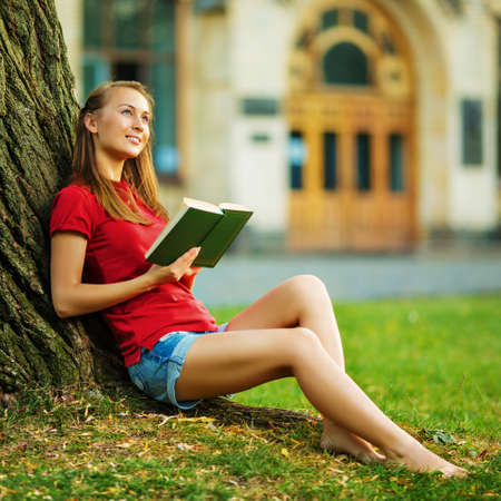 curiously: Young pretty student woman is sitting near the tree with a book in her hands and smiling and curiously looking in front of her in the university campus. Love to study concept.  Stock Photo