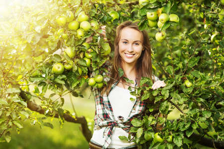Woman in a sunny apple tree garden during the harvest season. Young smiling beautiful woman is standing among the sunlit apple trees with ripe organic apples on it. Healthy country lifestyle concept.