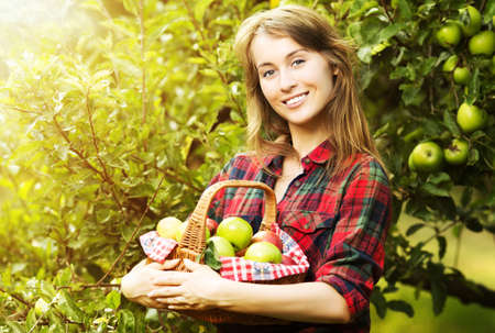 Woman with basket full of ripe apples in a sunny garden. Young smiling attractive woman is standing with full basket of organic apples in a sunlit orchard. Country happy lifestyle concept.  photo