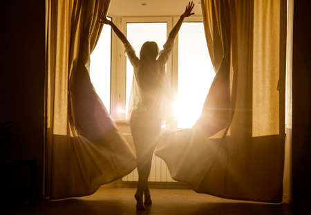 Woman in the morning. Attractive sexy woman with slender body is looking at the sunrise standing near the window in her home and having a perfect cozy morning. Standard-Bild