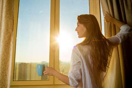 Mujer por la mañana. Atractiva mujer sexy con cuerpo limpio es la celebración de una taza de té o café caliente y mirando la salida del sol de pie cerca de la ventana de su casa y tener una mañana acogedora perfecta.