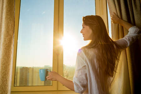Vrouw in de ochtend. Aantrekkelijke sexy vrouw met nette lichaam houdt een beker met hete thee of koffie en kijken naar de zonsopgang staande bij het raam in haar huis en met een perfecte gezellige ochtend.