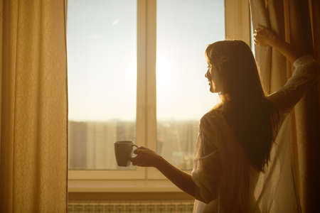 waking: Woman in the morning. Attractive sexy woman with neat body is holding a cup with hot tea or coffee and looking at the sunrise standing near the window in her home and having a perfect cozy morning.
