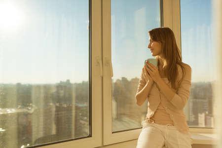 Mujer en la mañana. Tierna joven atractiva mujer es la celebración de una taza con té o café y mirando la salida del sol que se sienta cerca de la ventana de su casa y tener una mañana acogedora perfecta.