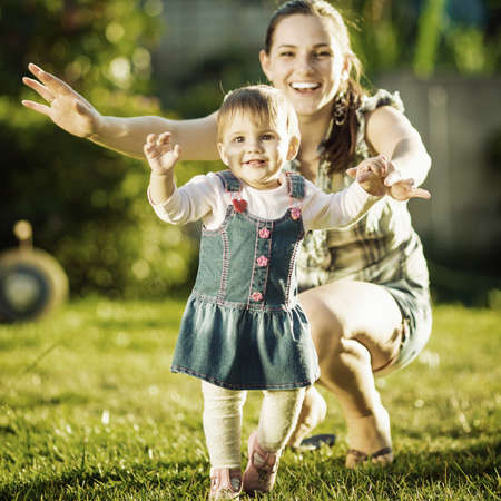 Baby girl is doing her first steps with mothers help. Cute little girl learns to walk with her young mom helping her in the sunny garden outdoors. Happy childhood and motherhood concept.