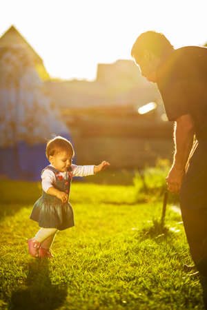 Baby girl is doing her first steps. Cute little girl is learning to walk and going to her grandfather in a sunny garden. Happy childhood concept. Standard-Bild