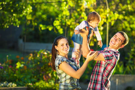 family garden: Happy young family having fun outdoors in summer. Mother, father and their cute baby-girl are playing in the sunny garden. Happy parenthood and childhood concept.