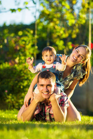 Happy young family having fun outdoors in summer. Mother, father and their cute baby-girl are playing in the sunny garden. Happy parenthood and childhood concept. Focus on the father. Stock Photo