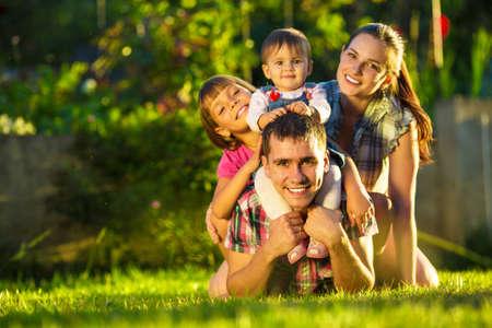 vida saludable: Familia joven feliz que se divierte al aire libre en verano. Madre, padre y sus pequeñas hijas lindas están jugando en el jardín soleado. Paternidad feliz y concepto de infancia. Se centran en el padre.