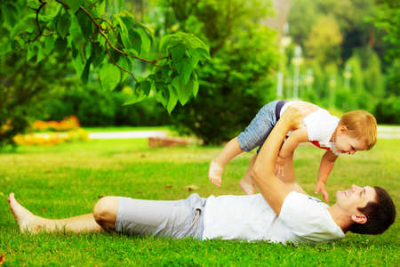 Happy father and son playing together having fun in the green summer park on a warm sunny day. Family and love concept. photo