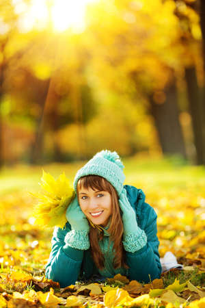 yellow trees: Beautiful happy young woman in the autumn park. Joyful woman wearing bright teal hat and scarf is having fun outdoors in a bright yellow trees. Colorful fall concept.   Stock Photo