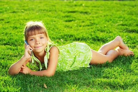 petite fille avec robe: Belle petite fille parle sur un téléphone et couché sur une herbe verte sur une journée d'été ensoleillée. Banque d'images