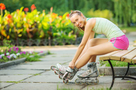 rollerskating: Athletic woman sitting on a bench in a park and putting on inline skates. Close up. Sport lifestyle.
