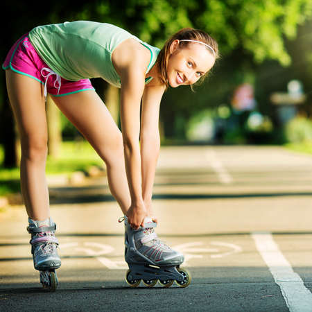 skating fun: Rollerblading woman. Young attractive female fitness model is having fun skating in a city park in the sunny morning. Sports lifestyle concept. Stock Photo