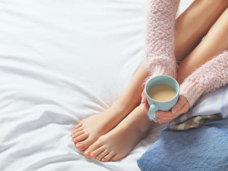 woman barefoot: Woman relaxing at cozy home atmosphere on the bed. Young woman with beautiful skin and nails with cup of cocoa or coffee in her hands enjoying comfort. Soft light and comfy beauty natural lifestyle.